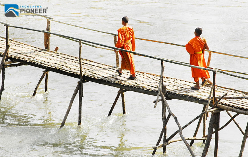 the monks crossing a wooden bridge in Luang Prabang, Laos